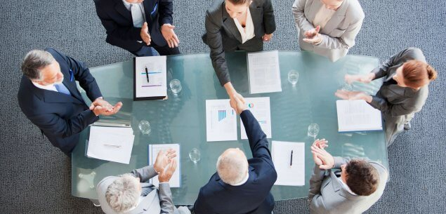 Eight business people standing around a table with documents shaking hands.