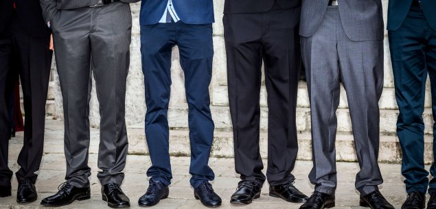 Six pairs of men wearing suits; image of legs standing in horizontal line.