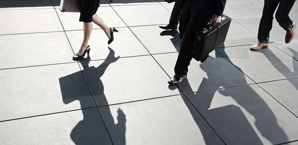 People with briefcases walking on sidewalk casting shadows.