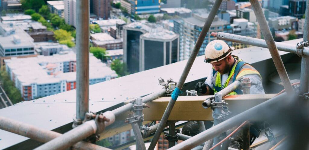 Construction worker working in rafters of building structure overlooking cityscape.