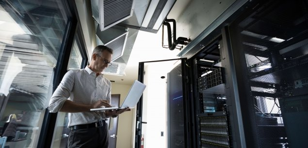 Systems administrator holding a laptop working on a server.
