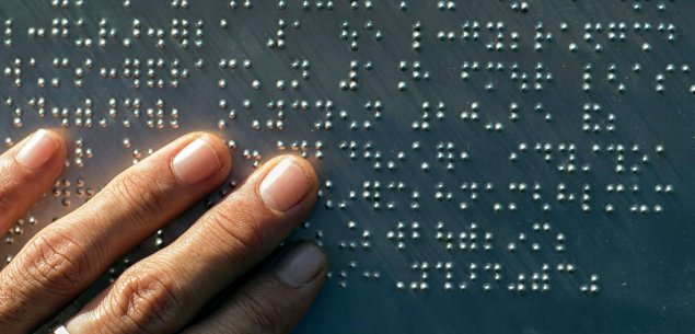 Hand reading braille.