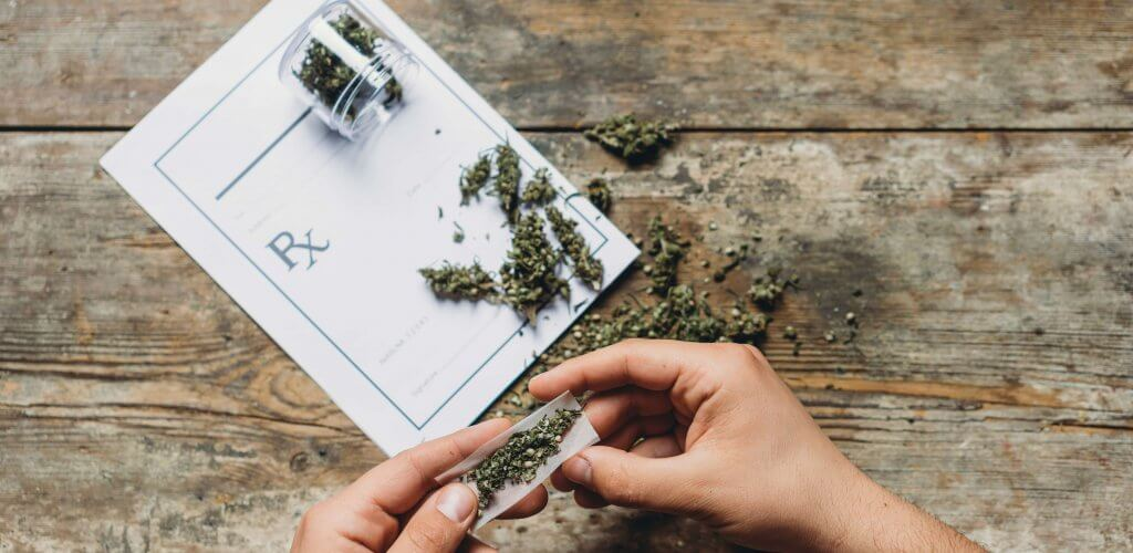 Person rolling marijuana joint.