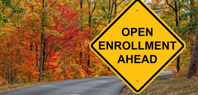 "Yellow street sign that says ""Open Enrollment Ahead"" on autumn road."