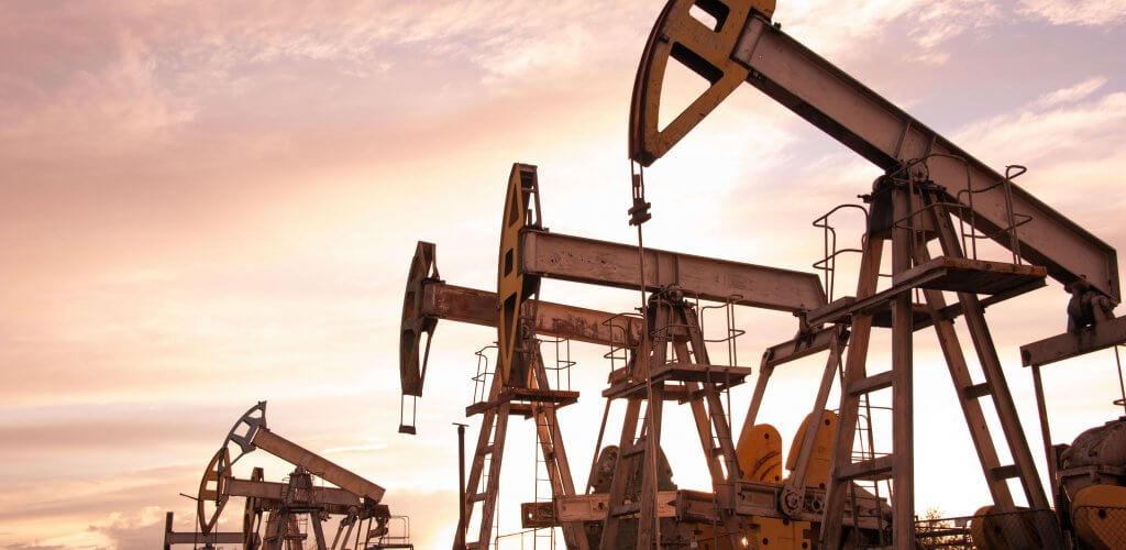 Oil pumps lined up against sunset landscape.