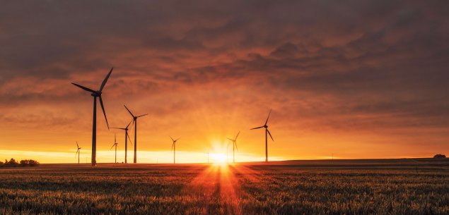 Wind turbines against sunset landscape.
