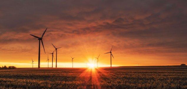 Wind turbines against sunset landscape.