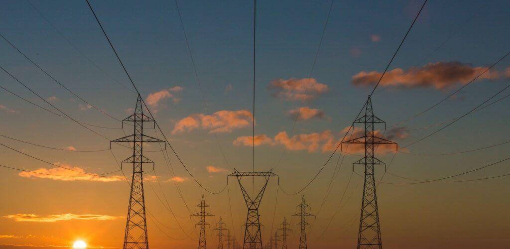 Power lines against sunset landscape.