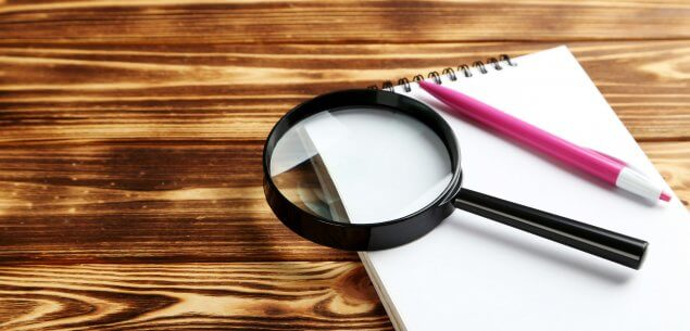 Magnifying glass on notepad on wooden desk.