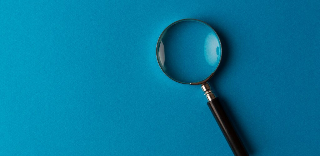 Magnifying glass against teal background.