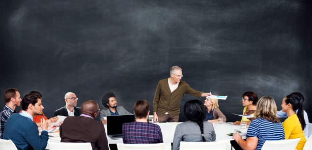 Teacher talking to group of students in front of chalkboard.