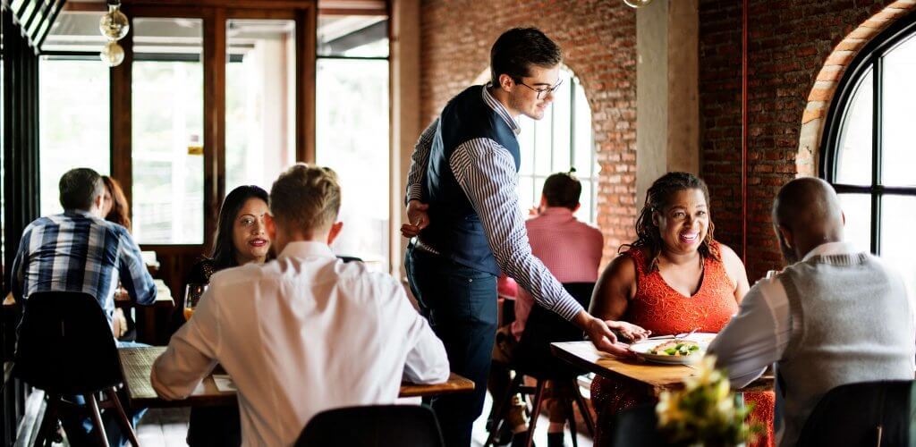 Waiter serving customers at busy restaurant.