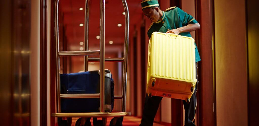Bellhop loading a cart with luggage.