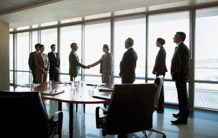 People standing around conference table shaking hands.