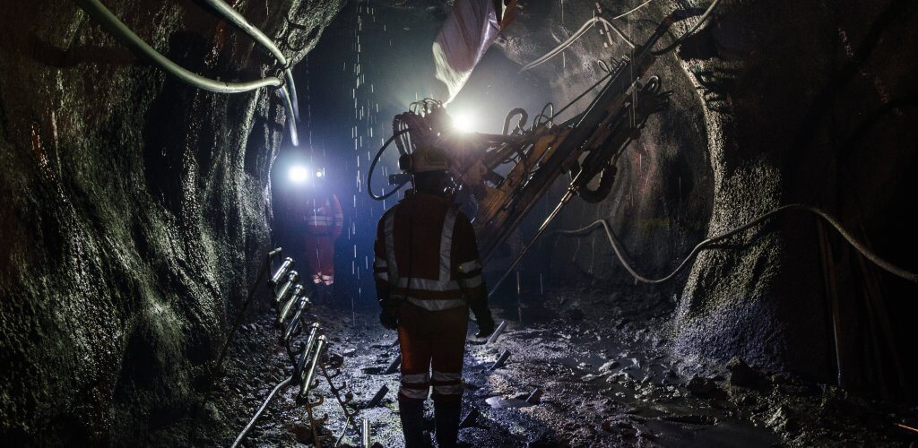 Man walking down a dark mine shaft