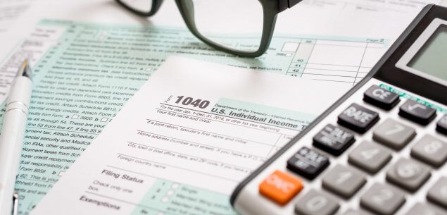 Tax document with reading glasses and calculator.