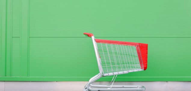 Shopping cart against green wall.