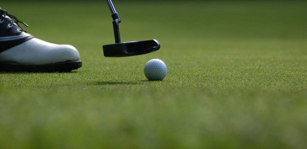 Close up of golf club hitting golfball on green.