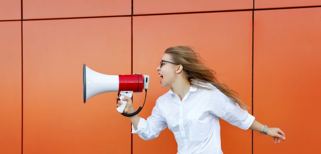 Woman with megaphone against orange wall.